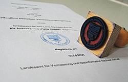 Ein auf die Seite gelegtes Dienstsiegel liegt auf einer gesiegelten Urkunde