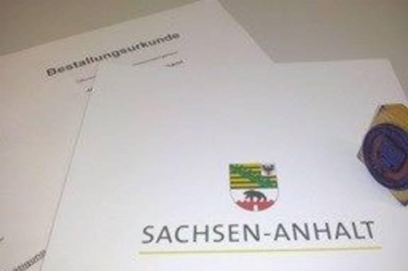 Foto: Ein auf die Seite gelegtes Dienstsiegel liegt auf einer gesiegelten Urkunde